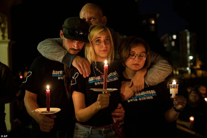 """Mack Lewis (left) Haley Adams (center) Emma Mitchem (right) and Nate Millsap (rear) comfort each other during a candlelight vigil Saturday in Vancouver, Wash., for Aaron """"Jay"""" Danielson, a supporter of Patriot Prayer"""