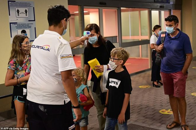 A family clad in face masks have their temperatures checked prior to boarding the MSC Grandiosa on August 16