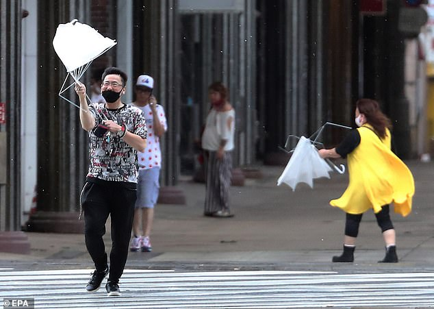 Pedestrians struggle with umbrellas against strong wind caused by typhoon Haishen in Kagoshima, Kagoshima Prefecture, southwestern Japan