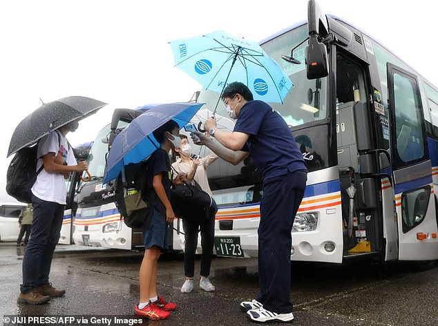 People undergo a temperature check before boarding a bus as an evacuation advice is issued due to the approach of typhoon Haishen in Hitoyoshi, Kumamoto Prefecture on September 6
