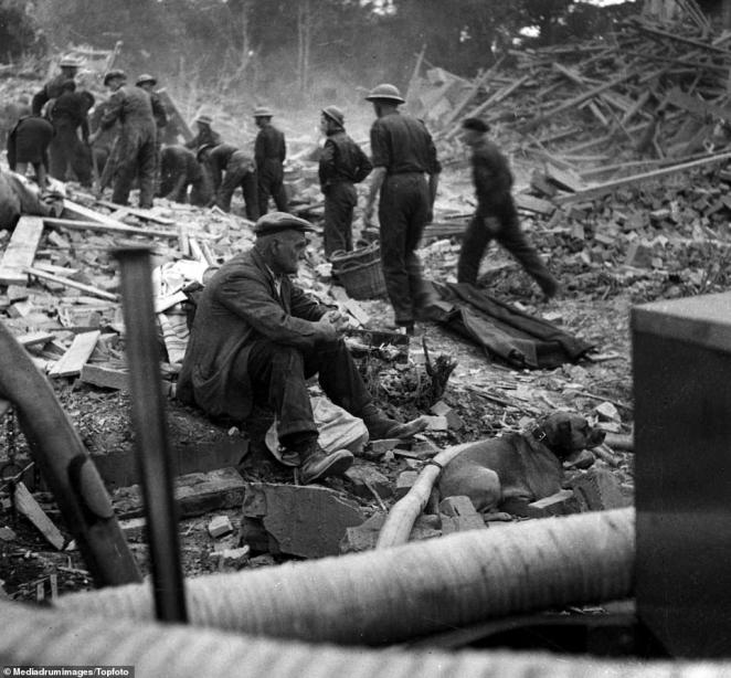 A widowed, elderly man sits in the rubble of his home after he went out to take his dog for a walk before finding his wife had died in his house when it was destroyed in a Blitz attack before his return. Around 13 Civil Defence workers sift through the wreckage in the background. The Civil Defence Service was a civilian voluntary organisation set up by the Home Office in 1935