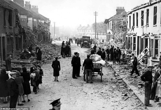Rows of houses lie destroyed on either side of the road in East Ham, east London, after an attack. Residents flocked into the streets to begin clearing the damage, as one man pushes a cart full of bagged debris. A policeman talks with one of the homeowners as people collect what remains of their belongings. East Ham South saw 89 high explosive bombs and eight parachute mines dropped during the Blitz, while East Ham Central saw 36 and 1 respectively