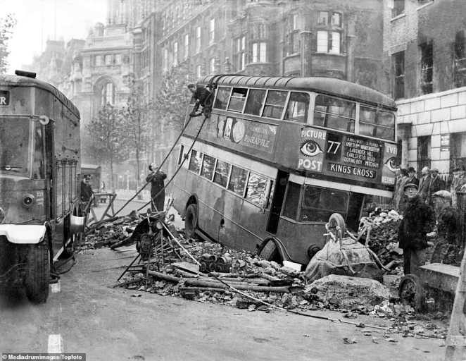 London transport workers try to retrieve a bus that had sunk into a hole when the road beneath it collapsed following a night of heavy bombing. The workers attach ropes and hooks to the top of the number 77 double-decker bus, which had fallen into a a whole in the road surrounded by rubble and an upturned. 'We can take it' became the catchphrase of Londoners during the Blitz, proving Hitler's belief he could terrorise the city from the air wrong