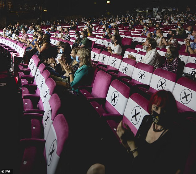 Accelerated plans by Culture Secretary Oliver Dowden and Prime Minister Boris Johnson could see theatres reopen without social distancing measures within weeks. Pictured: Audience members at the London Palladium sit with strict social distancing measures