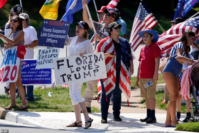 Dozens of Trump supporters clad in patriotic gear gathered outside his golf resort in Sterling on Sunday afternoon