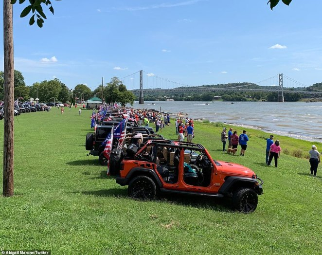 Pictured: local residents participating the Great American Boat Parade at the Ohio River parked along the shoreline and watched the boats sail by