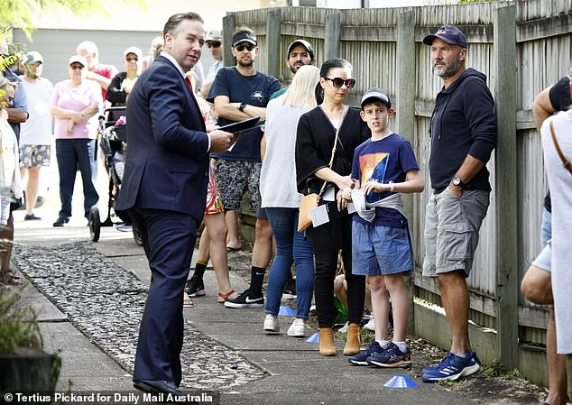Auctions in Victoria have virtually almost disappeared with the number of properties listed in Melbourne diving by 83 per cent in just one week. Pictured is an auction in Brisbane illustrating how Queensland is allowing socially-distanced bidding on site