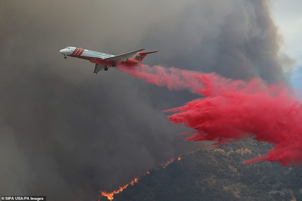 A fire fighting plane is seen dousing the area withspecially-formulated fire retardants designed to suffocate the sparks