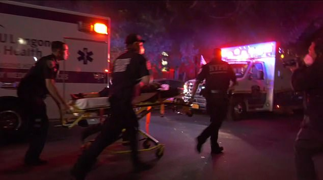 First responders are seen rushing one of the victims into an ambulance shortly after the shooting on Monday morning