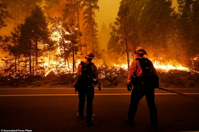 Firefighters keep an eye on the Creek Fire along state Highway 168, late on Sunday, September 6
