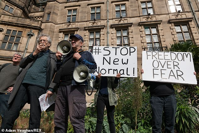 Protestors in Sheffieldhold signs saying 'stop new normal' and 'freedom over fear' as Piers Corbyn addresses the crowd