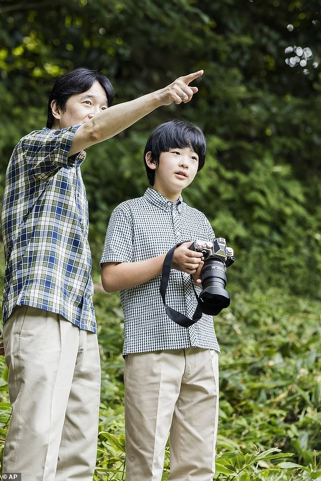 The Crown Prince of Japan points to something out of the frame, instructing his son on how to take a photograph of it