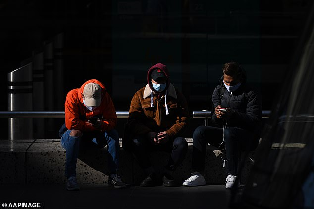 Pictured: Melburnians in face masks sit in the city on Monday
