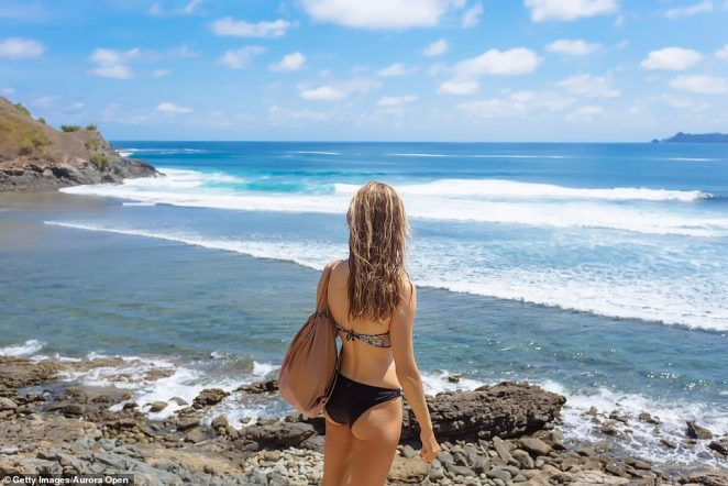 The tourist-hotspot attracts millions of foreign visitors each year - which grew 3.6 per cent to 6.3million in 2019. Pictured: A woman at Kuta, Lombok, Indonesia
