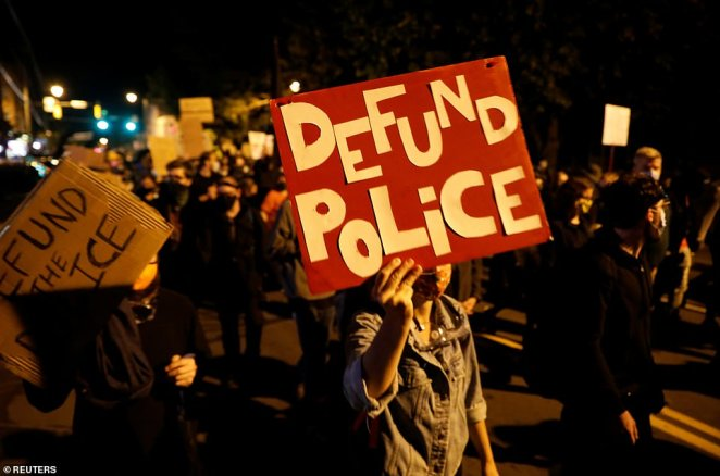 Two demonstrators hold up signs reading 'Defund The Police' on Sunday after protests sparked in Rochester, New York, this week