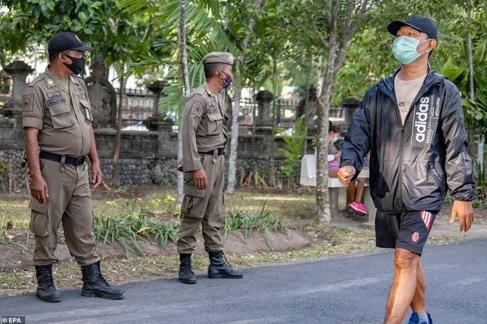 Masks were made mandatory in April but fines were enforced in Bali earlier this month. Pictured is a man wearing a face mask in Denpasar