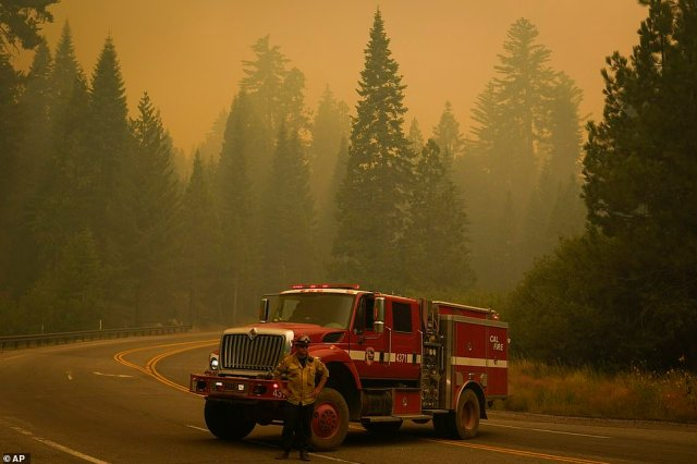 A firefighter stands in front of an engine on Highway 168 as crews monitor the advance of the Creek Fire on Monday