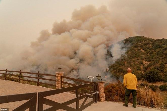 A firefighter monitors the El Dorado Fire as it burns a hillside near Yucaipa on Monday