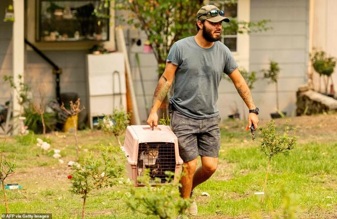 Residents evacuate with their pets during the Creek fire in the North Fork area of unincorporated Madera County on Monday