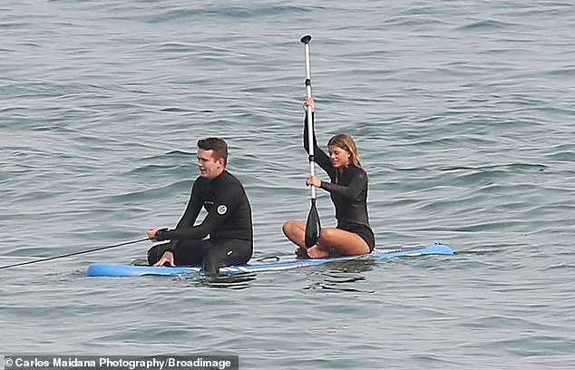 Switch up: After getting her fill of the surf life, Sofia and a male pal ventured back out into the ocean on a paddle board