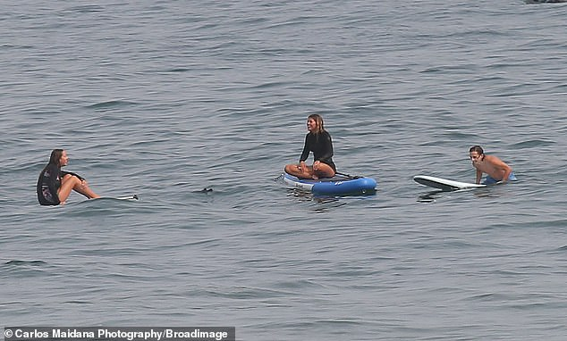 Hold up: Before reaching the sand, the duo stopped to talk to their fellow paddle boarding pals