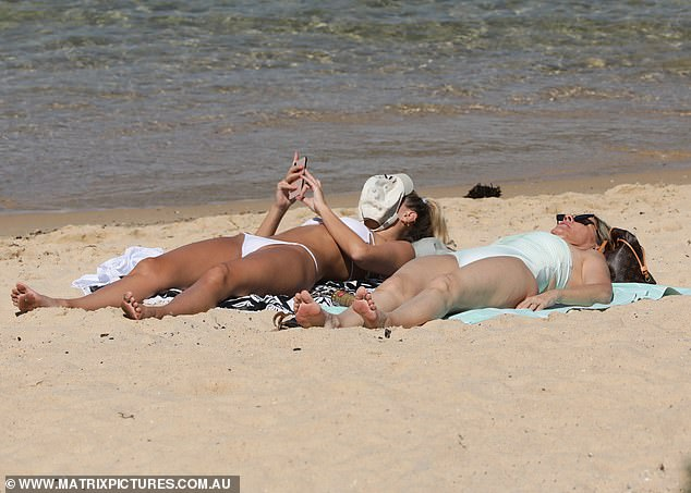 Shaded: Laura used a baseball cap to shield her face from the sun as she flipped through her phone