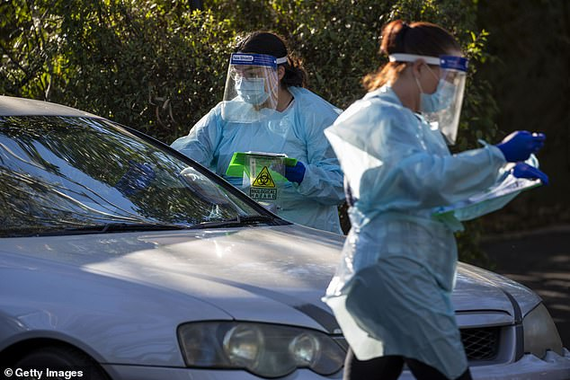 Nurses are seen doing COVID-19 testing at a drive-thru fever clinic in Ipswich on August 24, 2020 in Brisbane, Australia