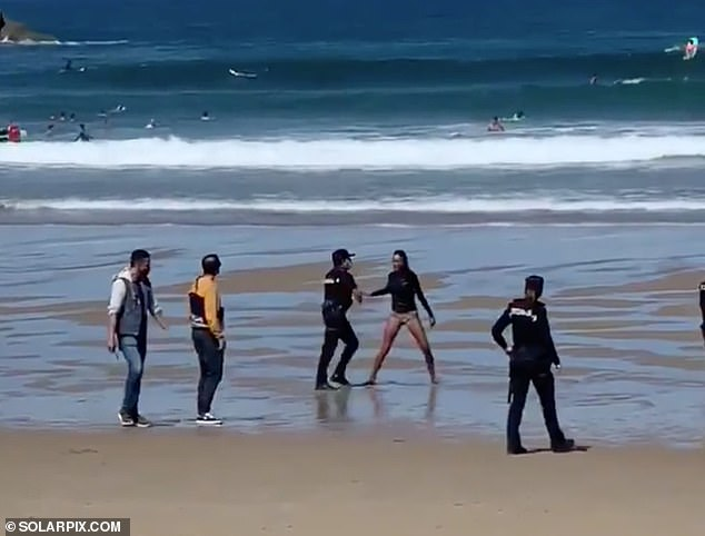 A woman (pictured centre wearing a neoprene top and bikini bottom) was arrested on a Spanish beach after going surfing while she was suffering coronavirus. Police handcuffed her on La Zurriola beach in the northern city of San Sebastian after she initially ignored their requests for her to return to shore
