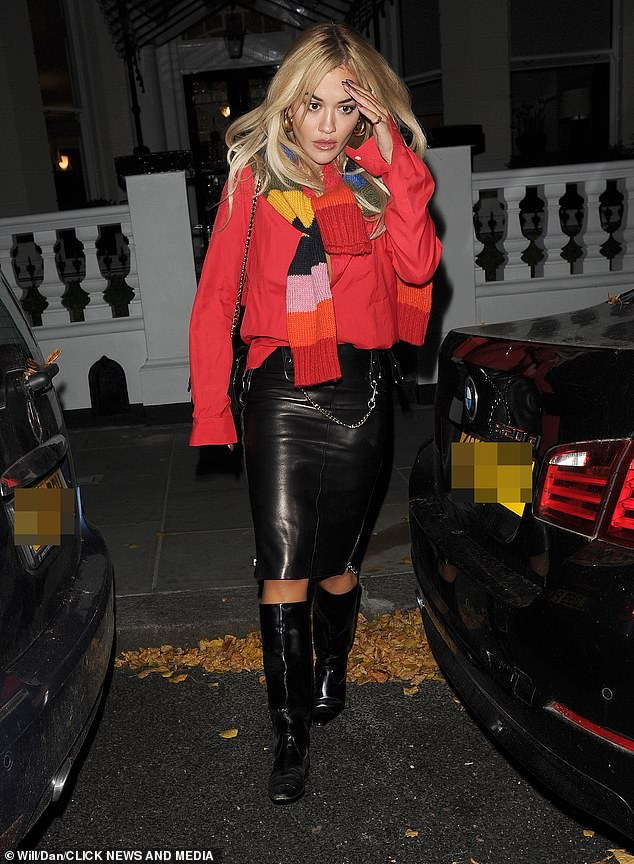 Casual: The singer teamed the scarf with a black leather midi shirt and a loose red jumper as she left her house for the evening
