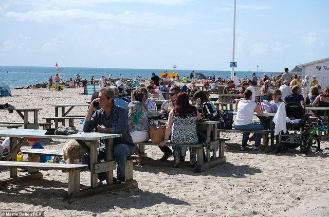 Crowds of people sit down to enjoy the sunshine in Mudeford in Dorset as warm air from the Atlantic makes its way to the country