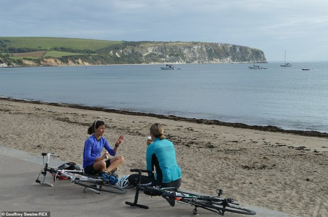 In Swanage, Dorset, cyclists sit down along the promenade to enjoy the sea air as showers begin to sweep across England and Wales