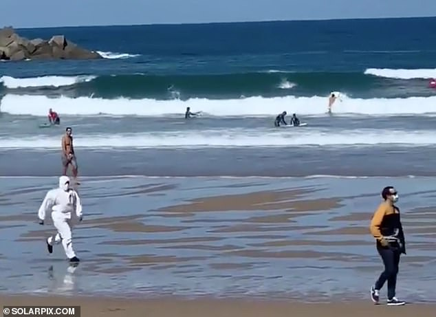Pictured: An officer wearing a hazmat suit runs down the beach towards the woman