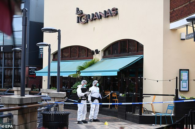 Two forensic officers behind a cordon near to Mexican chain restaurant Las Iguanas in Hurst Street, Birmingham, on Sunday