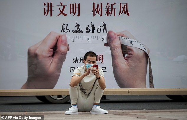 A city in China has sparked outrage after the authorities planned to score their citizens' behaviour through a smartphone app that monitors people's daily lives. The file picture taken on August 19 shows a Chinese man using his phone outside Beijing Railway Station