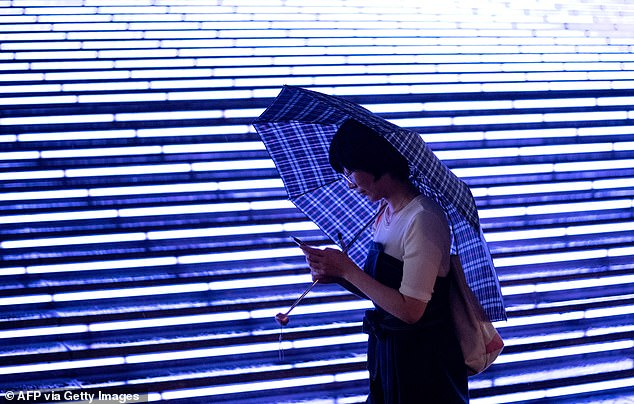 Each resident starts with a score of 1,000, with rewards and plus-points for volunteering, minus for running a red light, according to the app introduced by Suzhou officials. The picture shows a woman using her mobile phone outside a shopping mall in Beijing on August 18