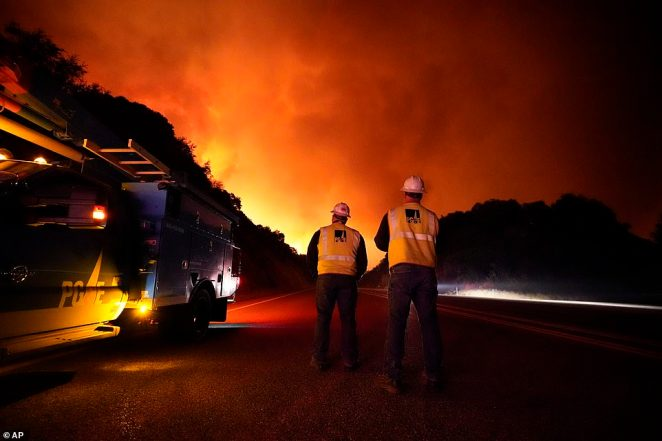 California's largest utility Pacific Gas and Electric has cut off power to 172,000 customers to avoid creating additional blazes. Pictured: Workers stand along Highway 168 as the Creek Fire advances on Tuesday
