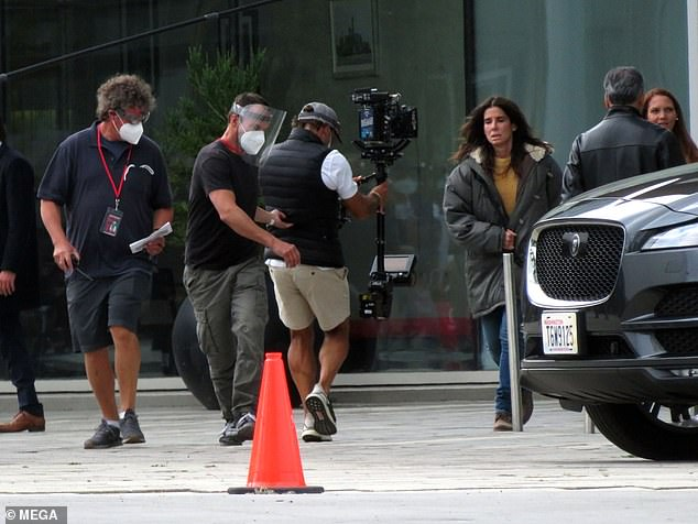 Cameras rolling: Sandra wore a mustard yellow sweater, a fur lined jacket, jeans, and boots as she briskly walked across the film set with a look of concern on her face