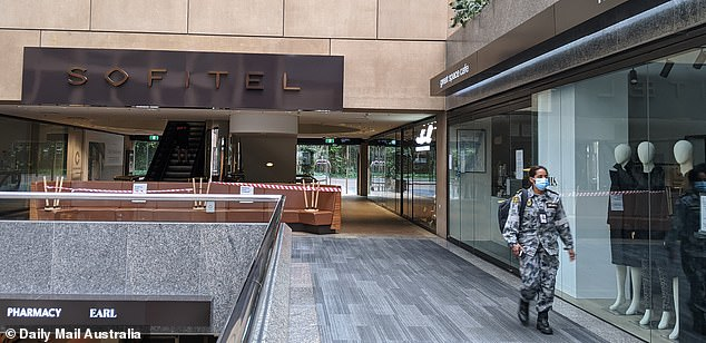 An ADF member walks past shops outside the Sofitel hotel in Melbourne on Wednesday