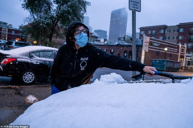 Alex Avery brushes snow off his car in Denver, Colorado on Tuesday as the record temperatures in the west gave way to snow