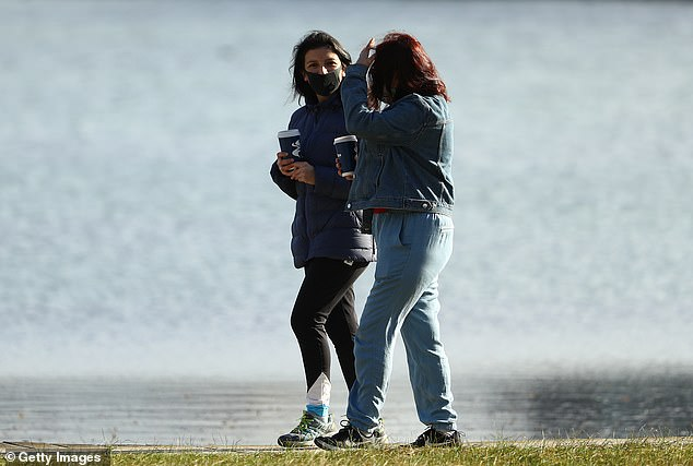 Two women wearing face masks walk with take away cups on Albert Park Lake on Wednesday