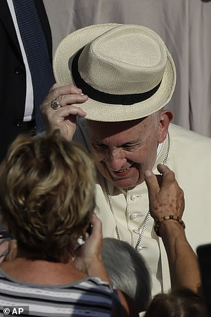 The Pope playfully tries on a hat given to him by a follower