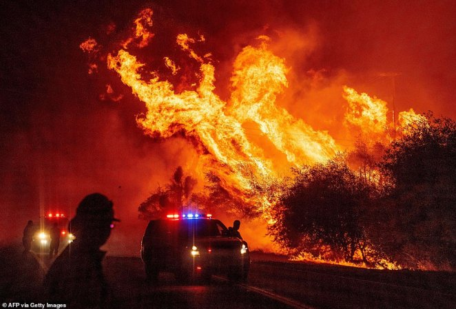 Law enforcement officers watch flames into the air as the Bear Fire continues to spread in Oroville, California, on Wednesday