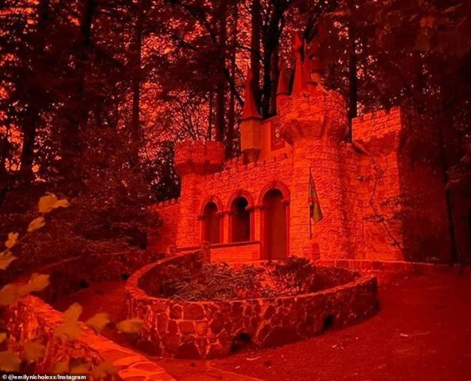 A castle nestled in the Oregon woods is seen glowing red as wildfires rage across the state