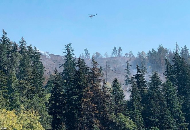 """A helicopter flies over fires burning on a ridge in Sumner, Washington. The governor said Wednesday, warning: """"This could be the greatest loss of human life and property due to wildfire in our state's history."""""""