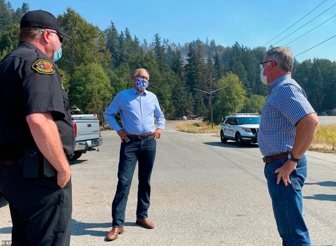 Washington Gov. Jay Inslee, center, talks to East Pierce Fire & Rescue Chief Bud Backer, left, and Pierce County Executive Bruce Dammeier about wildfires in the area