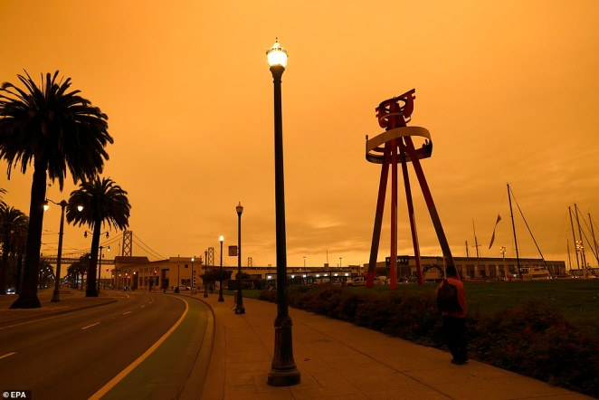 An orange sky in the early afternoon with the San Francisco Bay Bridge in the background as seen from King Street in San Francisco