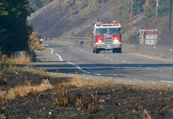 Heat rising from the roadway blur the image of a fire truck driving through a burned out area in Bonney Lake, Washington south of Seattle