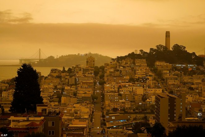 Looking down Lombard Street, Coit Tower on Telegraph Hill at right and the eastern span of the San Francisco-Oakland Bay Bridge, are darkened by wildfire smoke