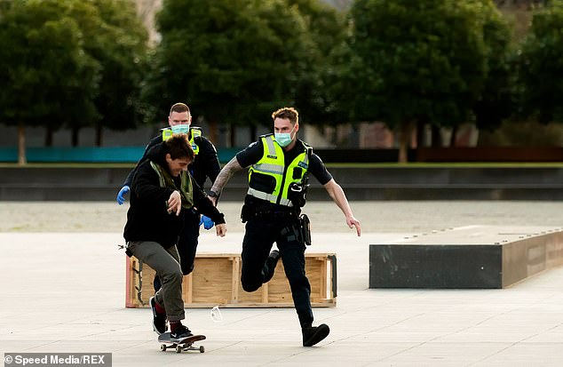 Pictured: Police are pictured chasing a skateboarder who is not wearing a face mask in Melbourne
