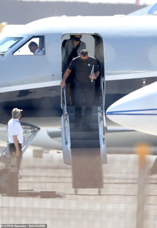 Hopped off the plane: Alex followed behind the actress as they returned to LA